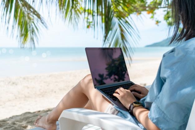 mujer-que-usa-computadora-portatil-telefono-inteligente-trabajar-estudiar-vacaciones-cady-fondo-playa_176697-333